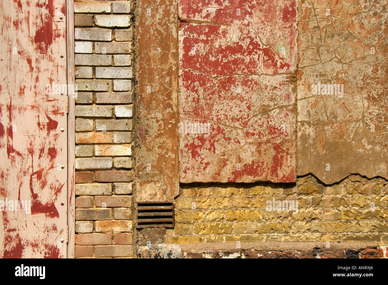 an abstract view of a dilapidated brick wall with crumbling cement and plaster - Stock Image