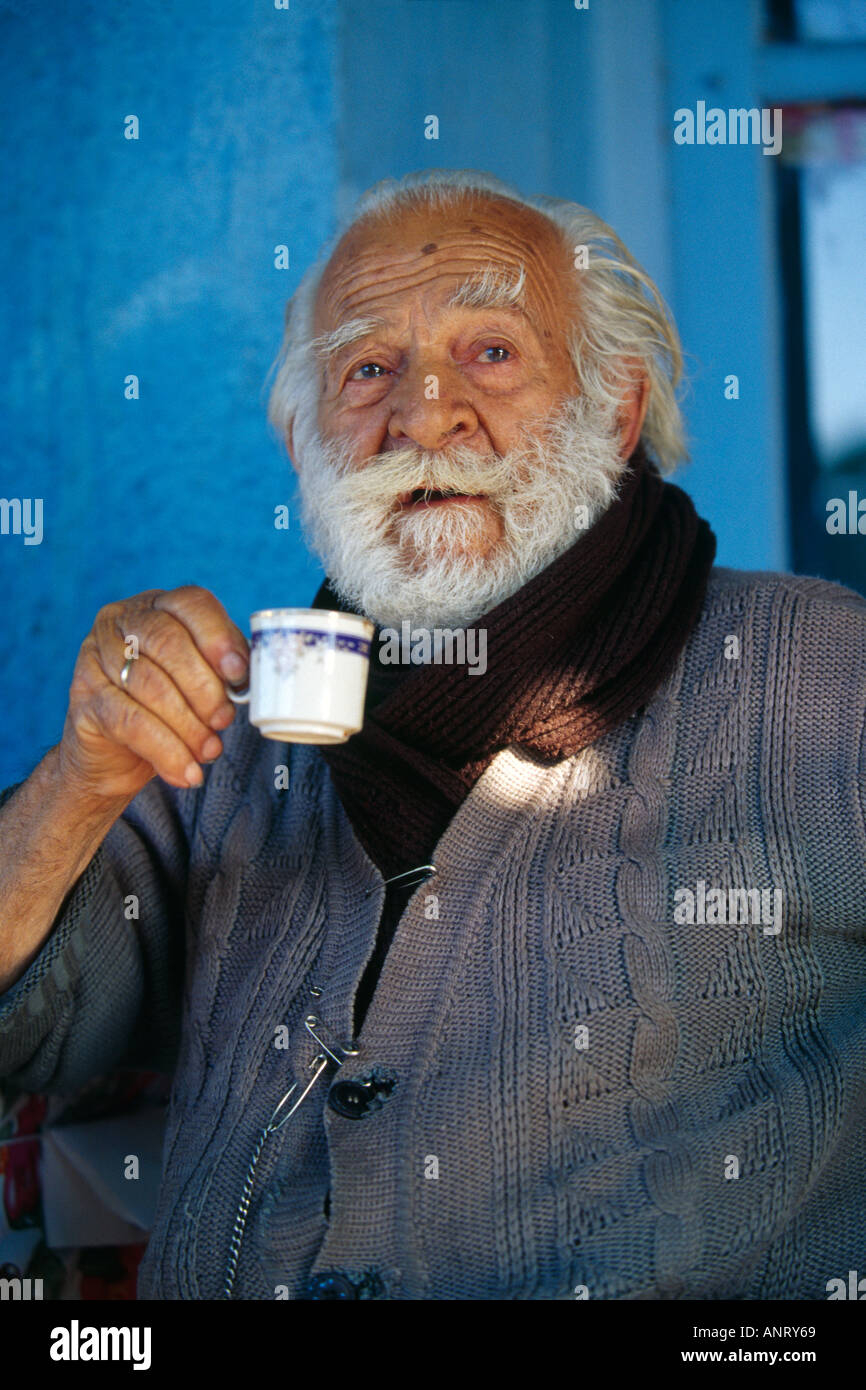 Lesbos Greece Old man with white beard, in his hand a small cup turkish  greek coffee
