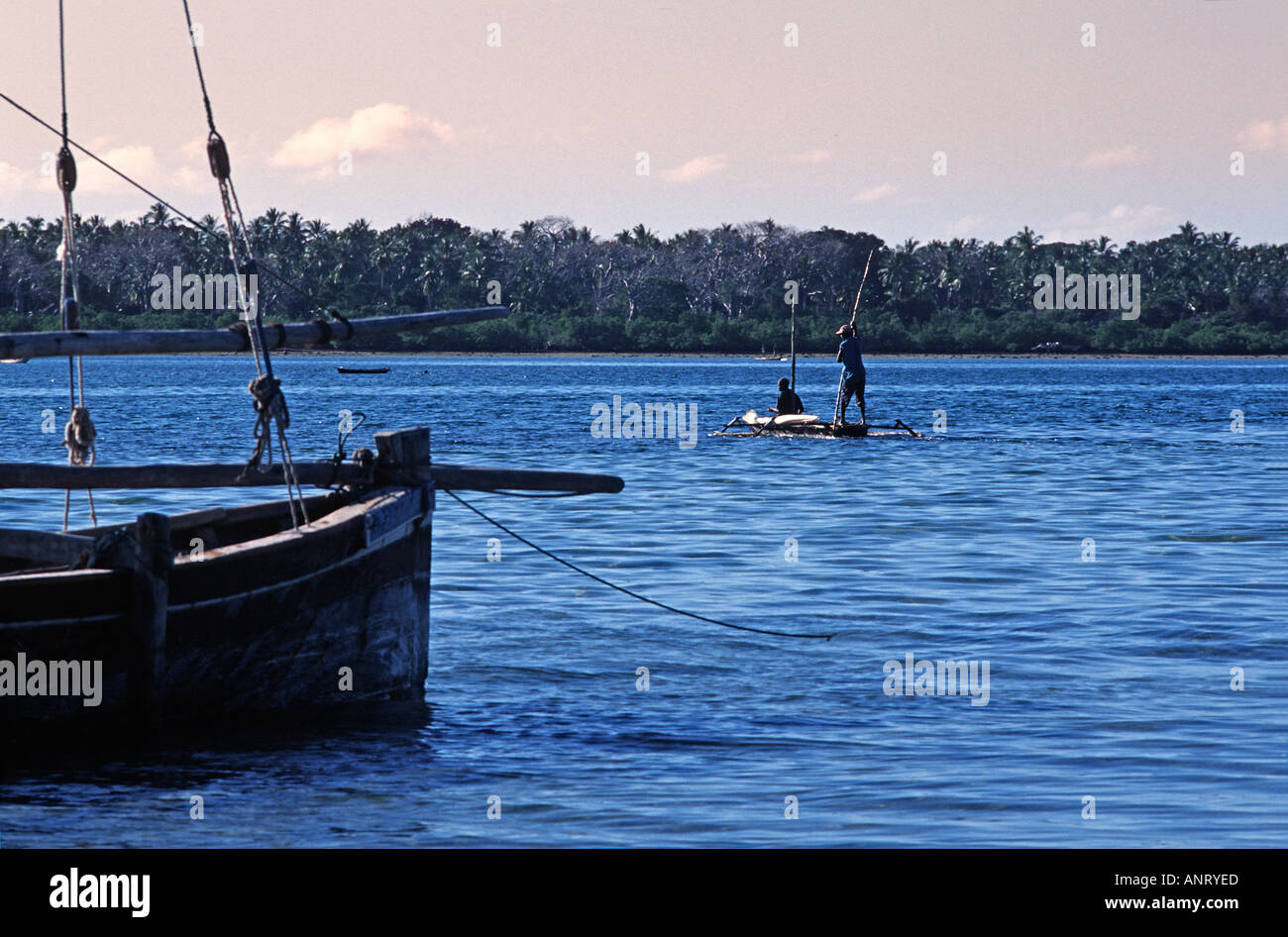 Tanzanian fishermen in their outrigger canoe seen beyond a dhow moored in the straits between Chole and Mafia Island TANZANIA - Stock Image