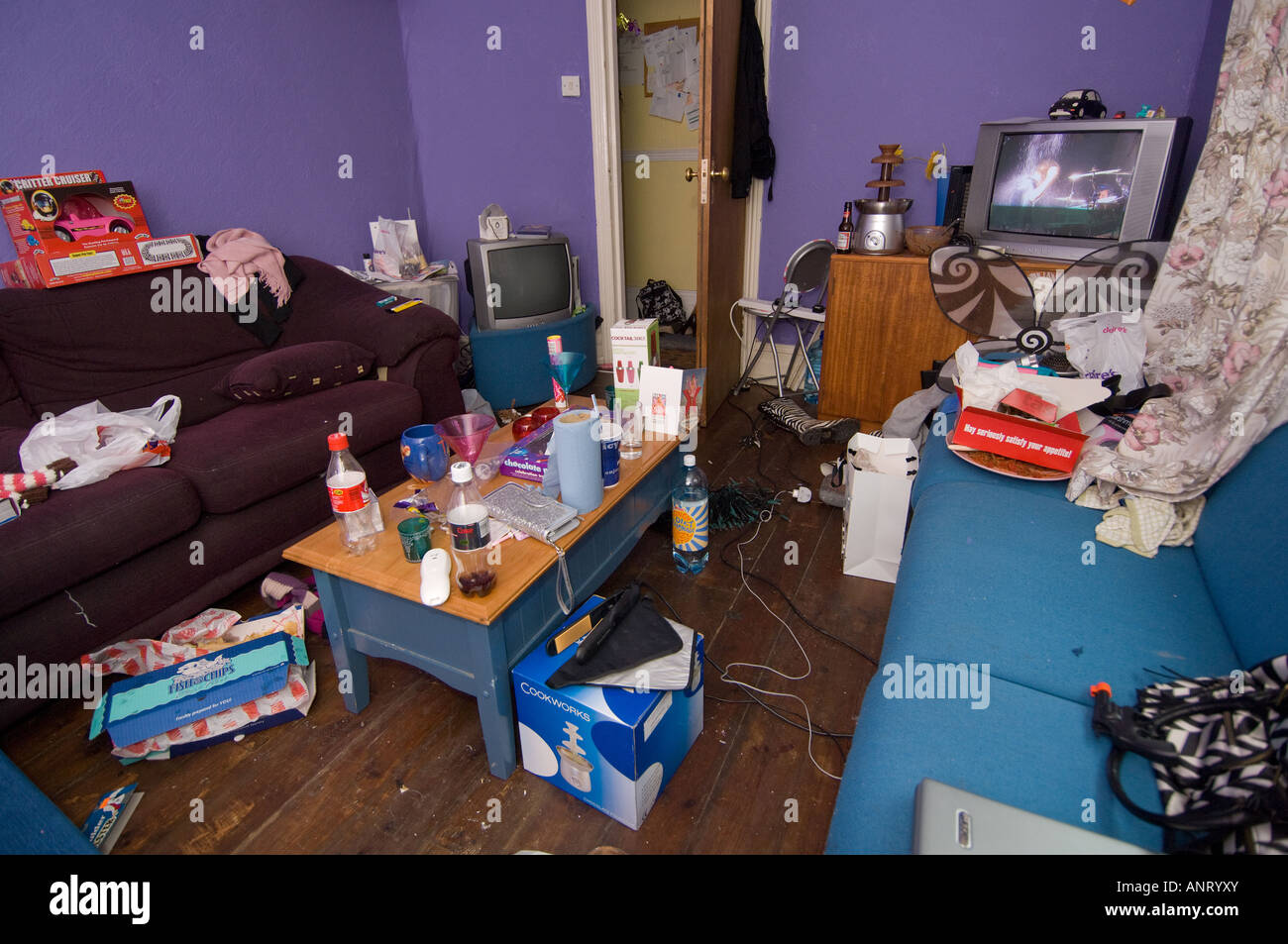 An untidy living room lounge in a student house the morning after a party, UK - Stock Image