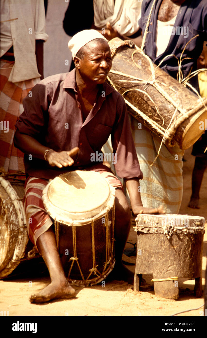 A musician playing traditional hand played drums at a Swahili wedding in Witu a small village on the coast of Kenya East Africa - Stock Image