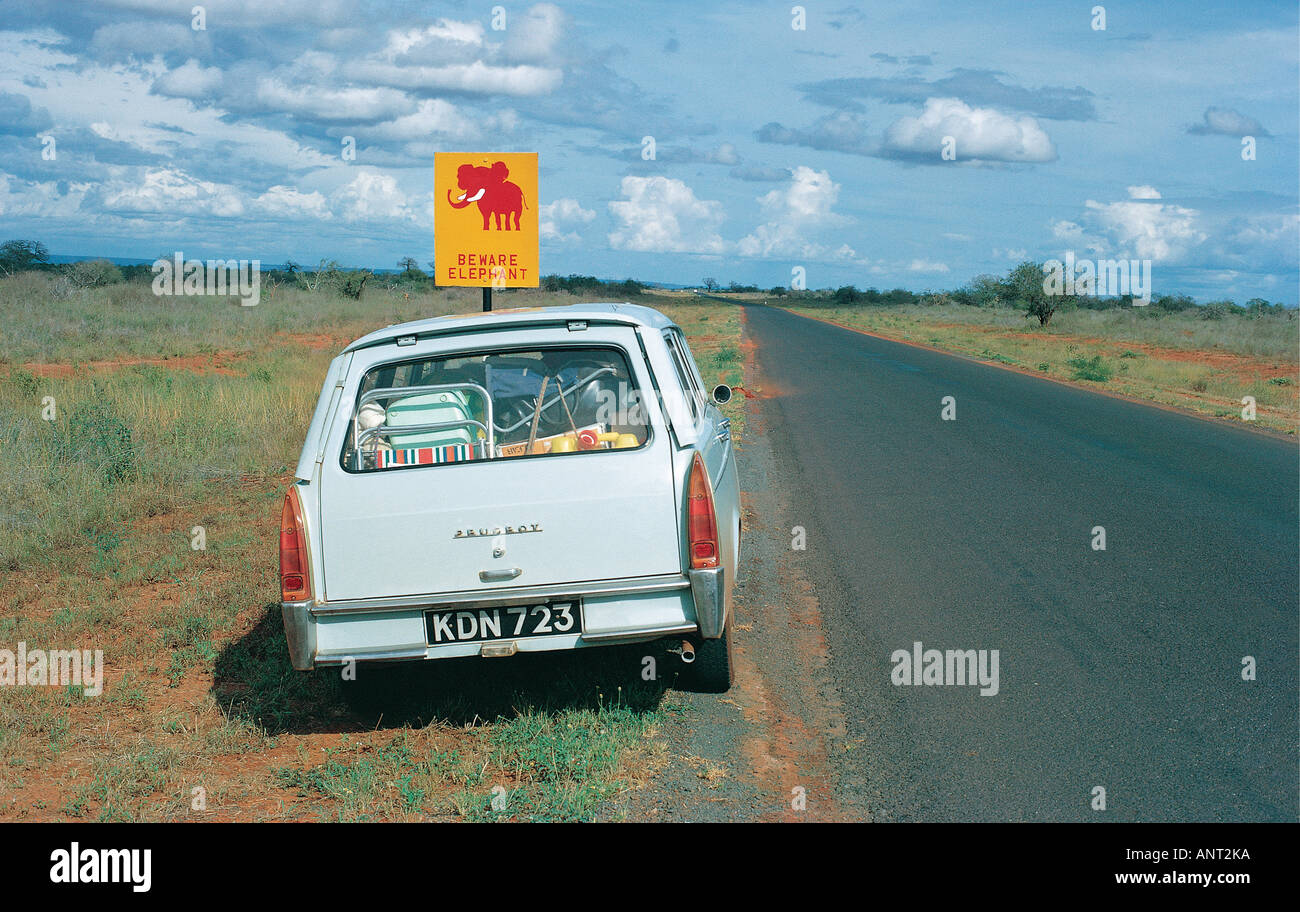 Peugeot 404 station wagon parked on the main Nairobi Mombasa road next to a road sign reading BEWARE ELEPHANT Kenya East Africa - Stock Image
