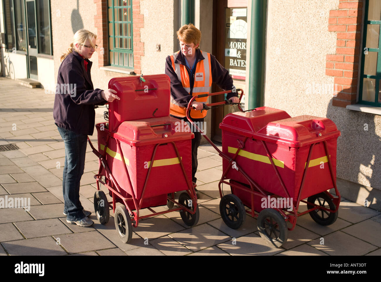 Two  2 women postal workers with red handcarts full of letters delivering the christmas post Aberystwyth Wales UK - Stock Image