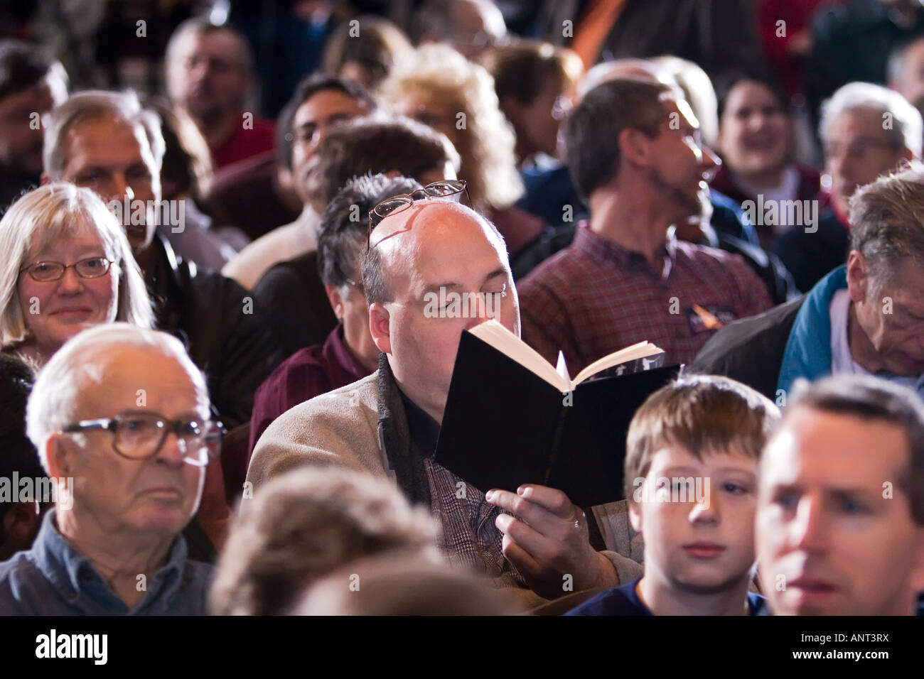 Man in crowd reads a book - Stock Image