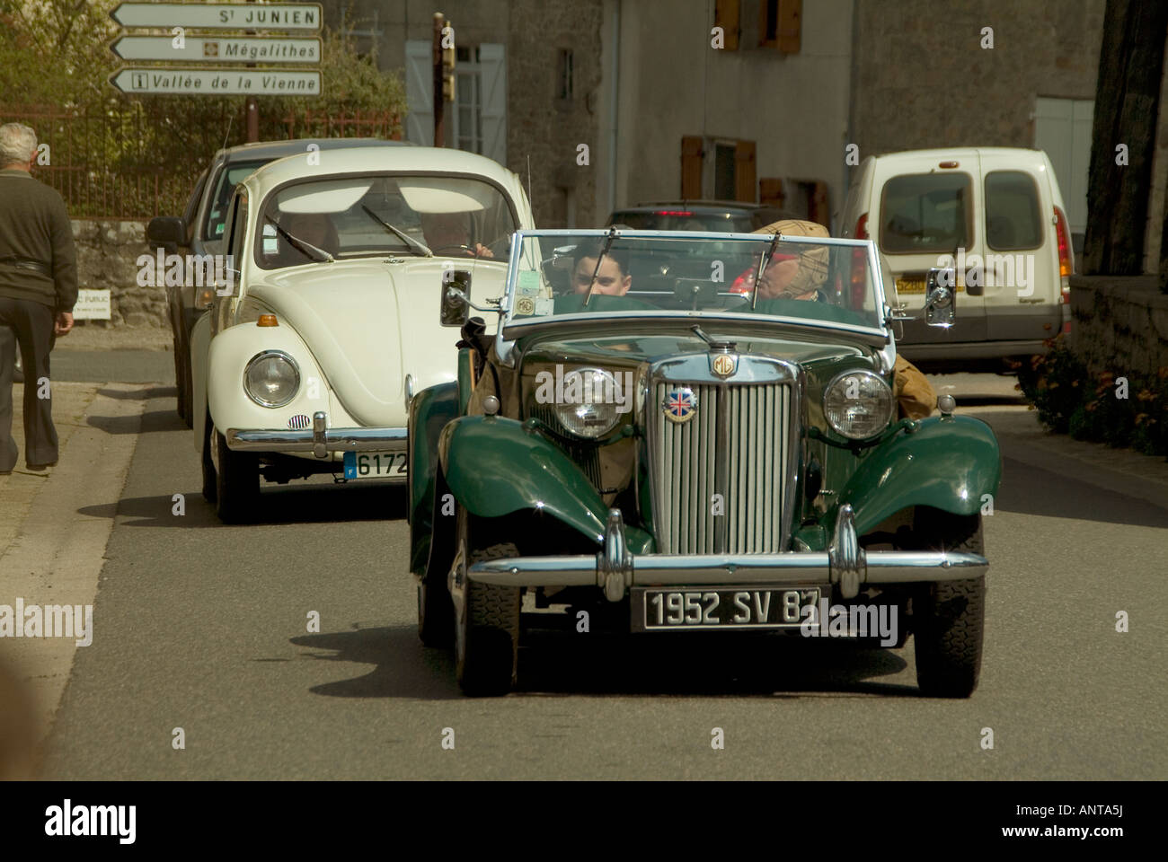 MG TF car followed by a classic VW beetle in a classic car road event in central France - Stock Image