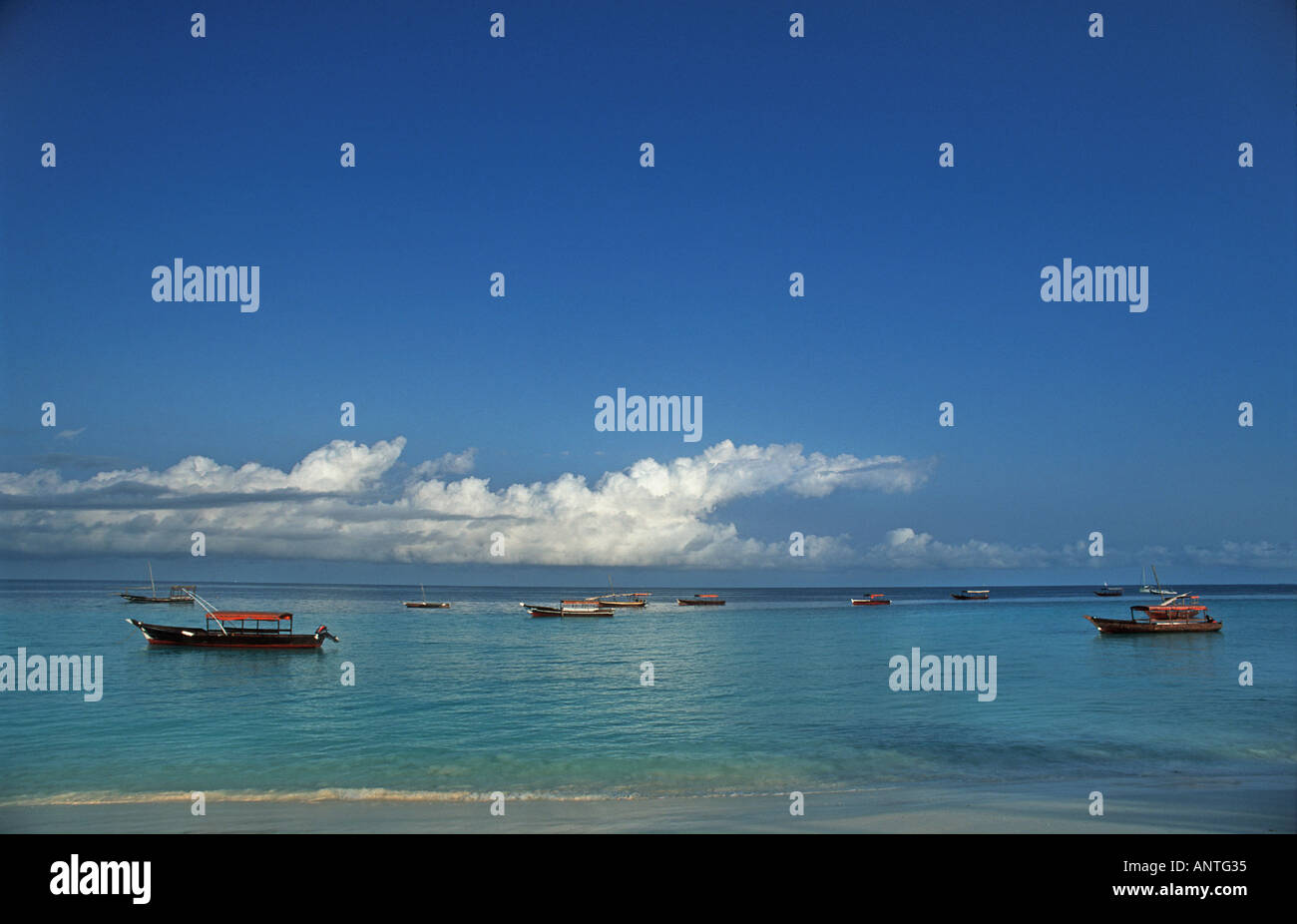 Boats moored off shore at low tide Nungwi Northern tip of Zanzibar Tanzania East Africa - Stock Image