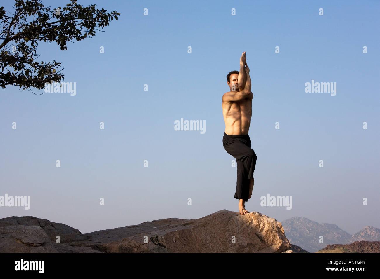 Man performing Hatha Yoga Garudasana eagle pose on a rock in India - Stock Image