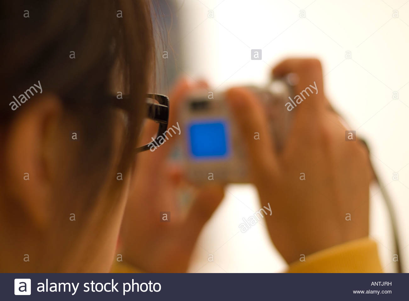 A young lady taking a digital picture - Stock Image