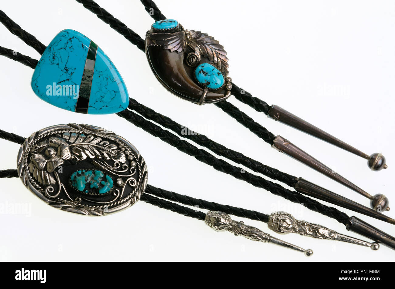 Close up of three silver  bolo ties with turquoise inlay on a white background - Stock Image