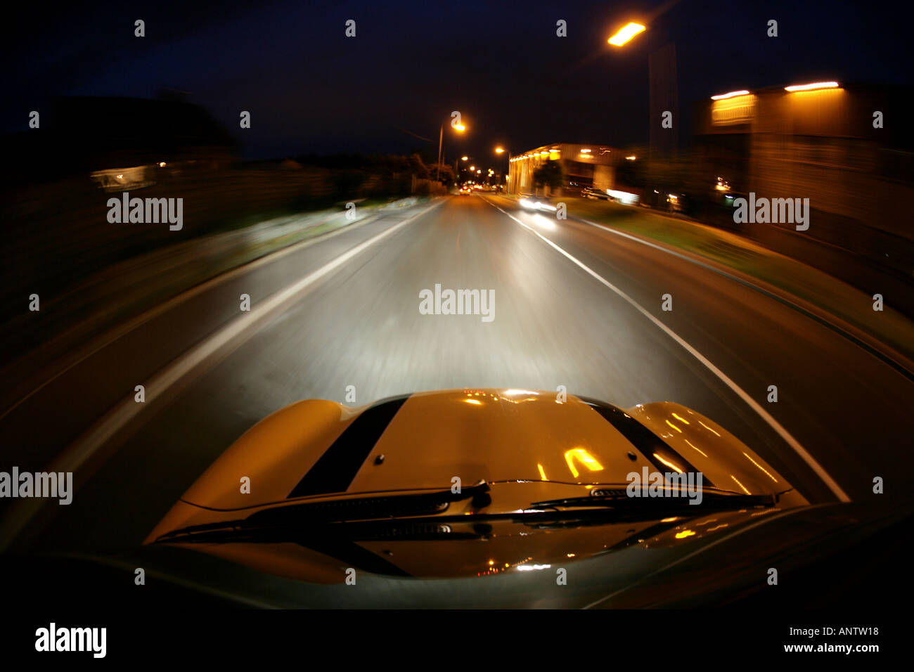 mini cooper convertible soft top driving at night - Stock Image