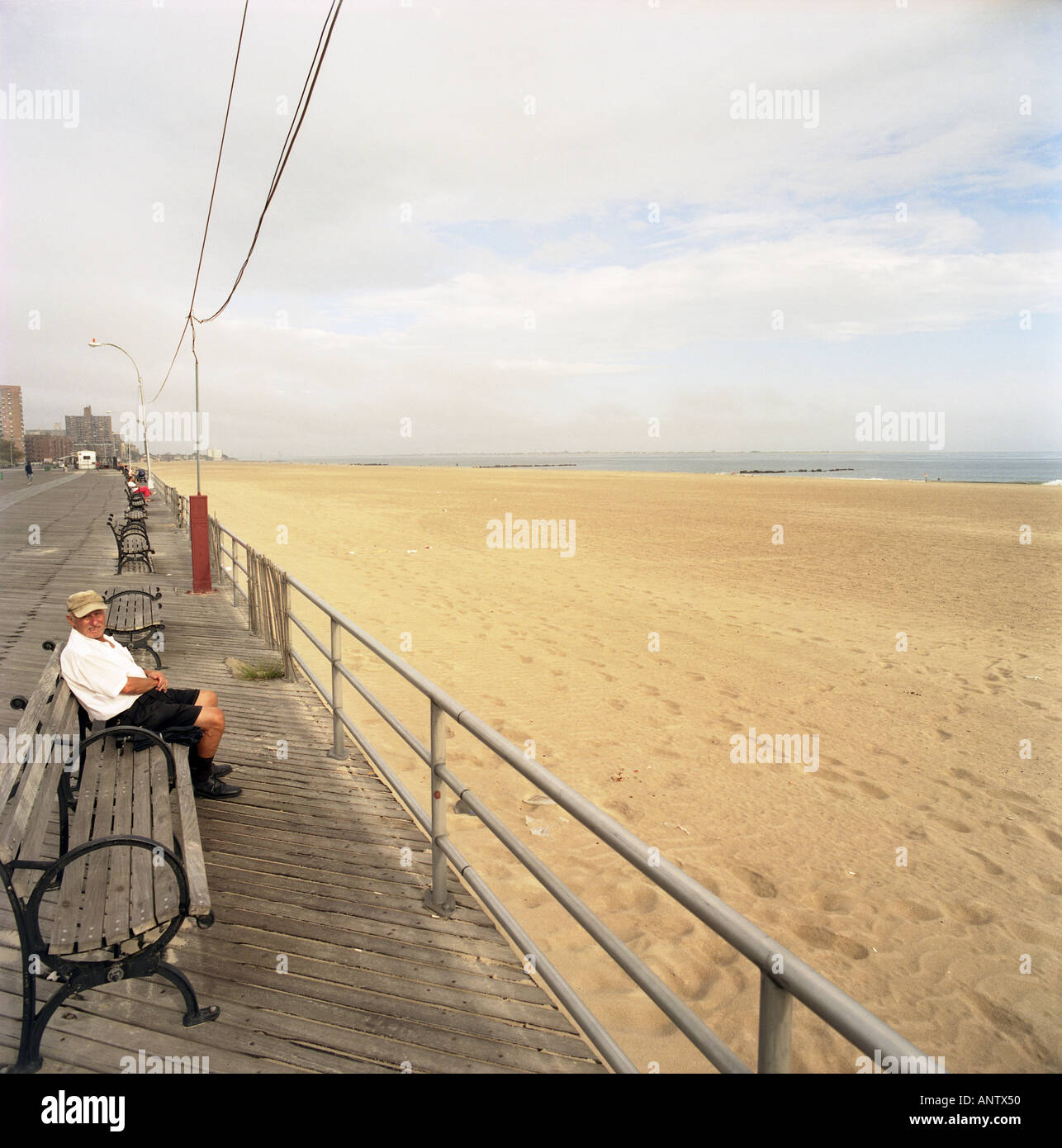 Elderly Person Is Sitting Alone On A Bench Chair In Front Of The Sea Along Pathway Coney Island Brooklyn New York City Usa