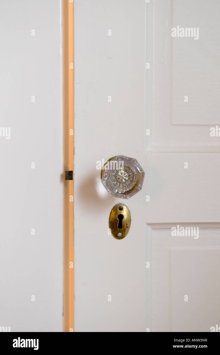 Antique glass door knob and brass keyhole on a white wooden door