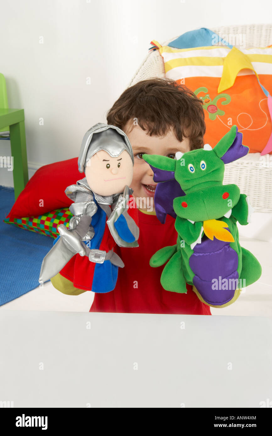 6598f99110df a boy smiles as he plays with a knight and a dragon hand puppet ...
