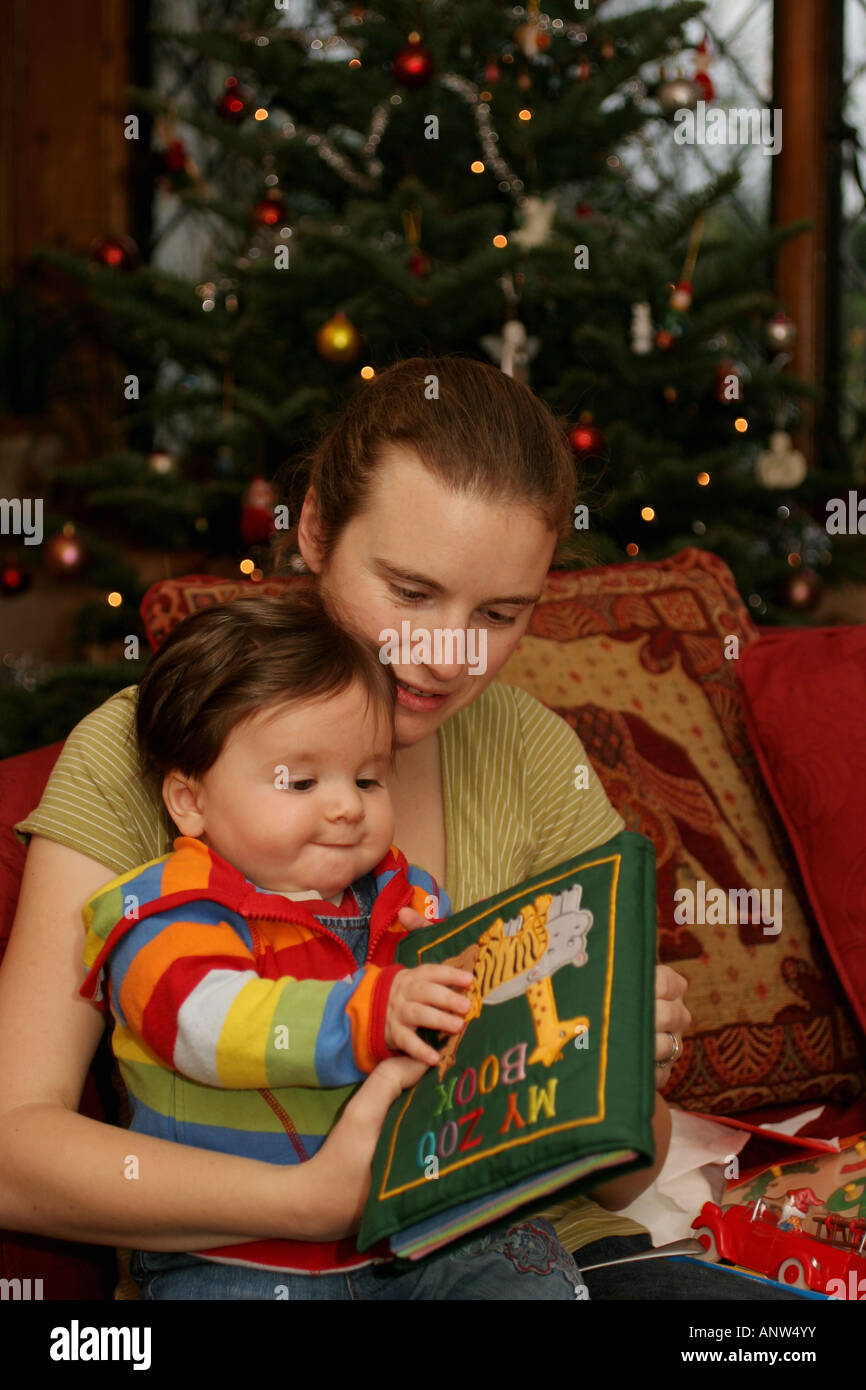 Baby Boy Looking at Book with Mother at Christmas - Stock Image