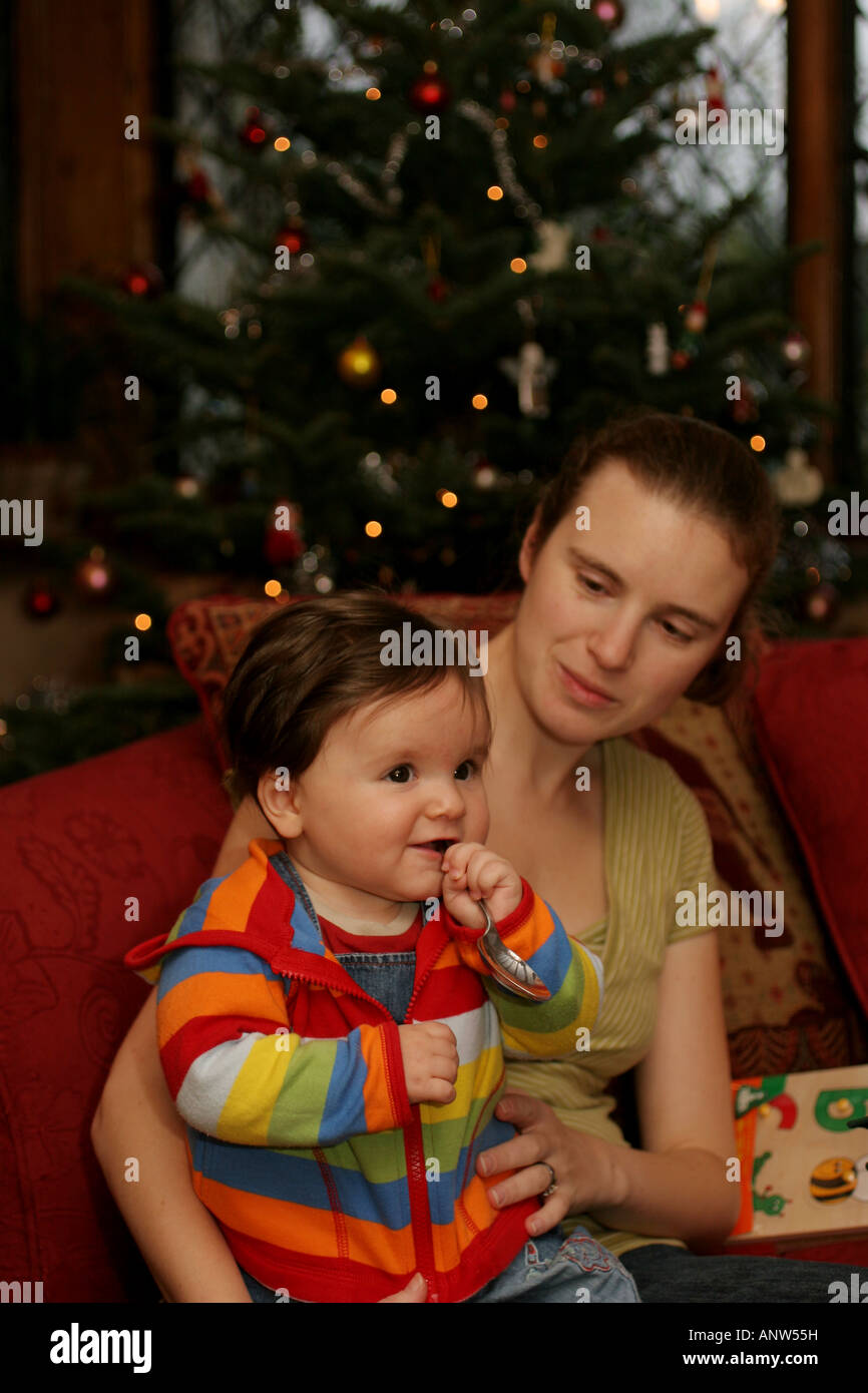 Baby Boy Holding Spoon with Mother at Christmas - Stock Image