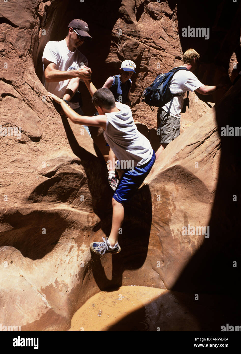 Hiker climb over a pond in the Peek a Boo Slot canyon, Great Staircase-Escalante NP, Utah, USA Stock Photo