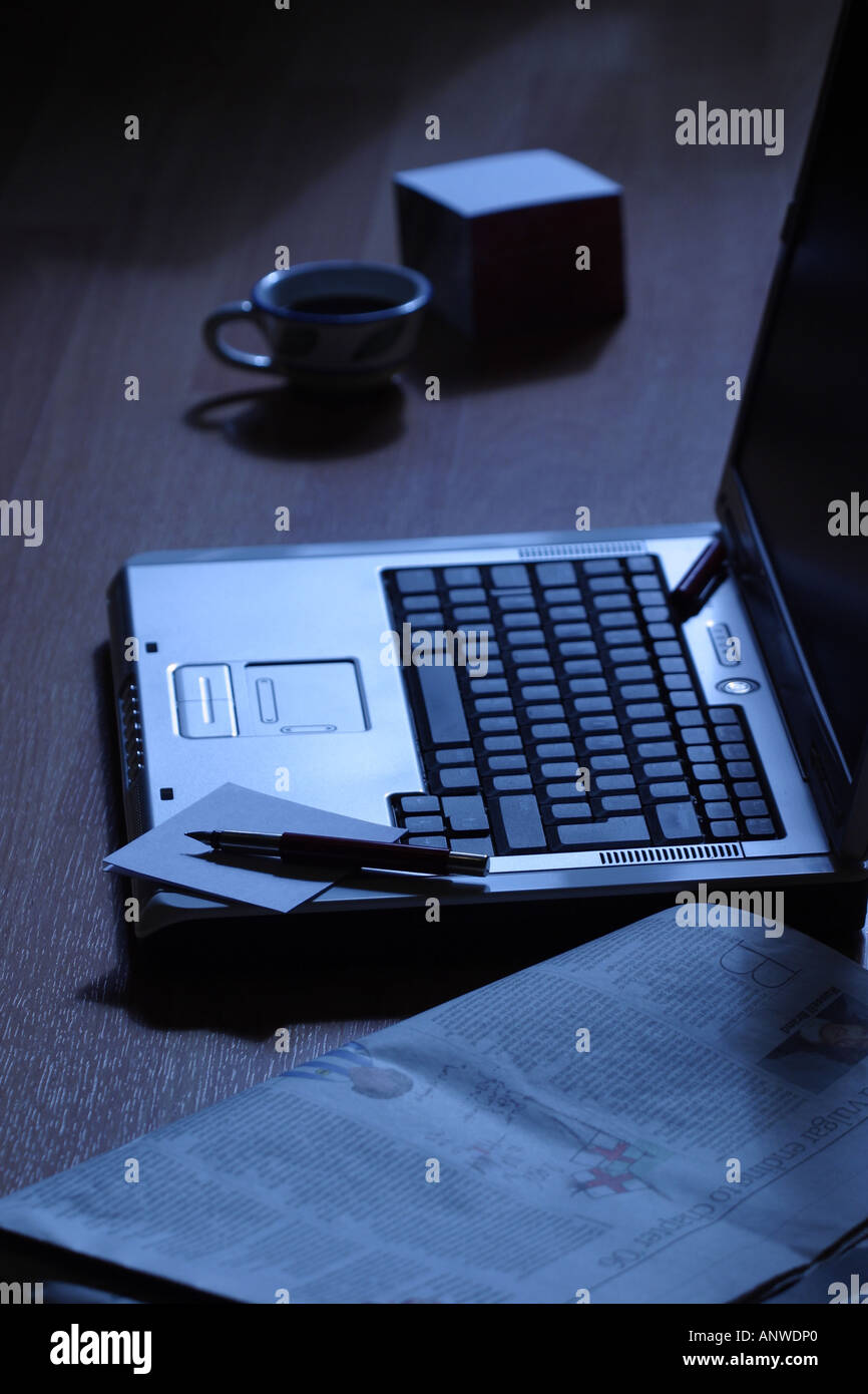 Early morning laptop computer on wooden floor with fountain ink pen newspaper paper notepad and coffee cup - Stock Image