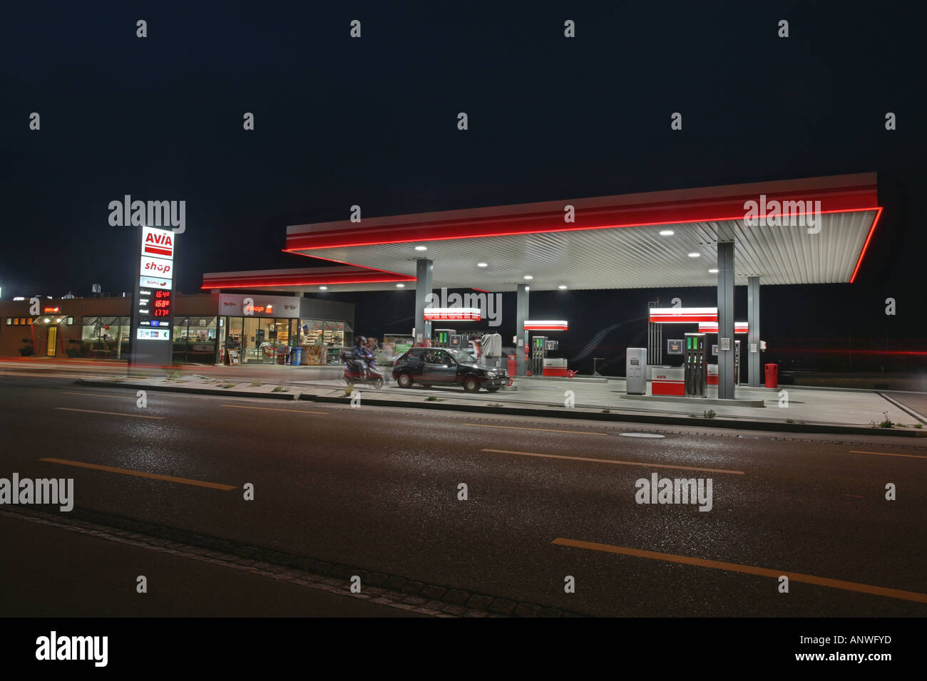 DRI of an Avia gas station illuminating a wide road at dusk - Stock Image