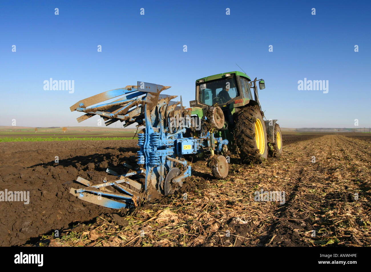 Tractor with plough in a field - Stock Image