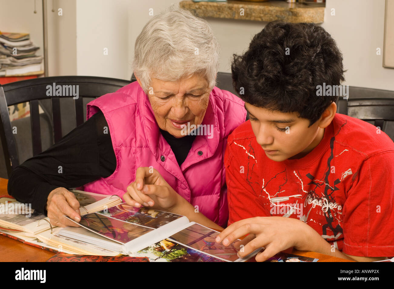 Senior woman grandmother looking at family photographs in albums with 13 year old teenage grandson vertical - Stock Image