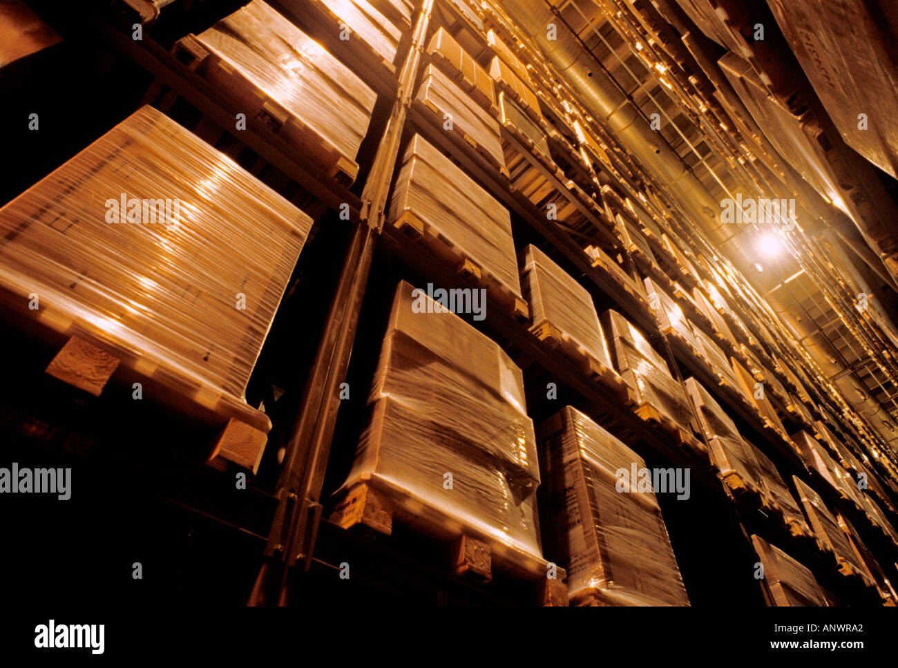 Shrink wrapped product stacked on pallette awaiting distribution in fully automated modern high bay warehouse - Stock Image