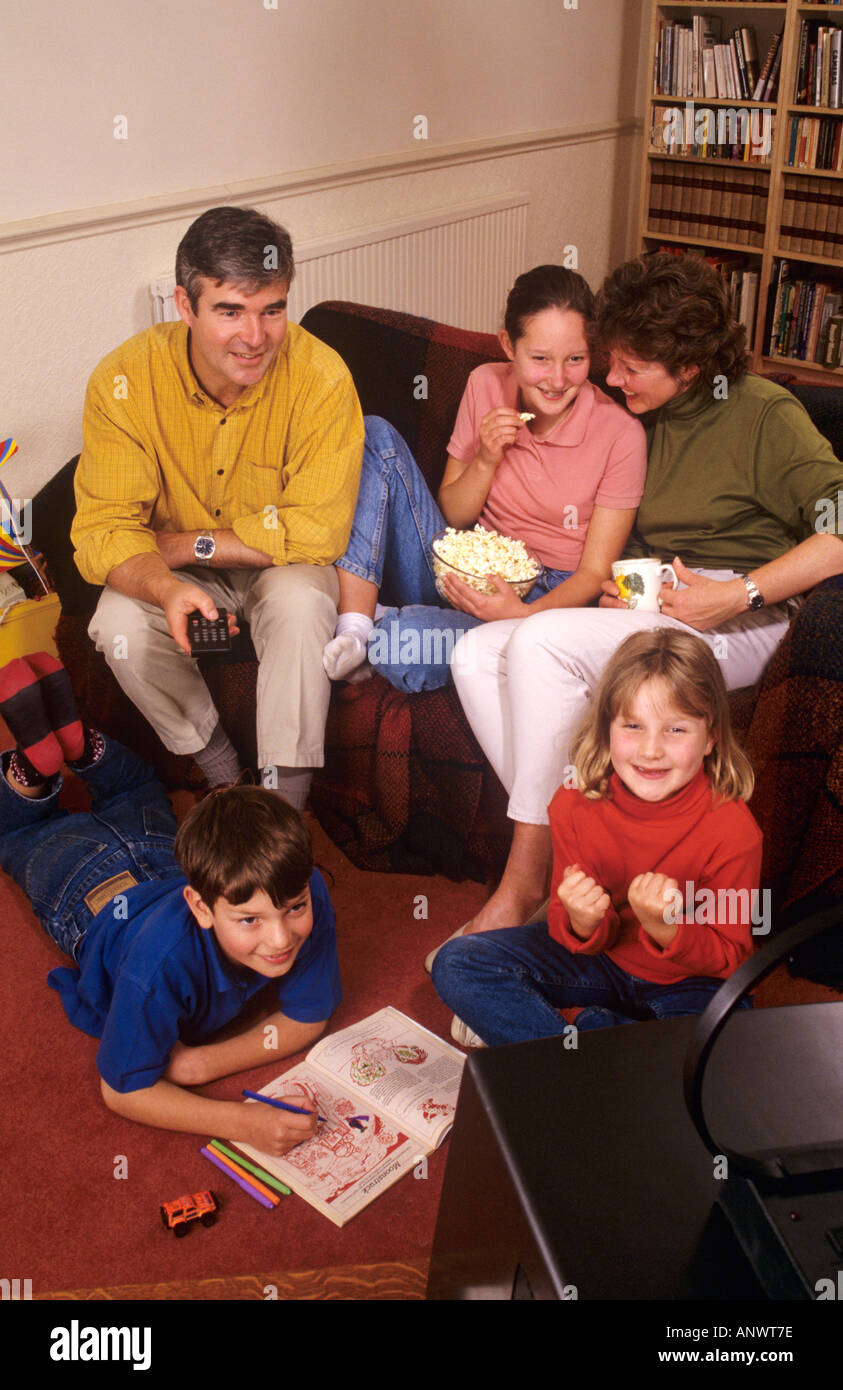Happy family of five at home sitting watching small portable television in their family room together - Stock Image
