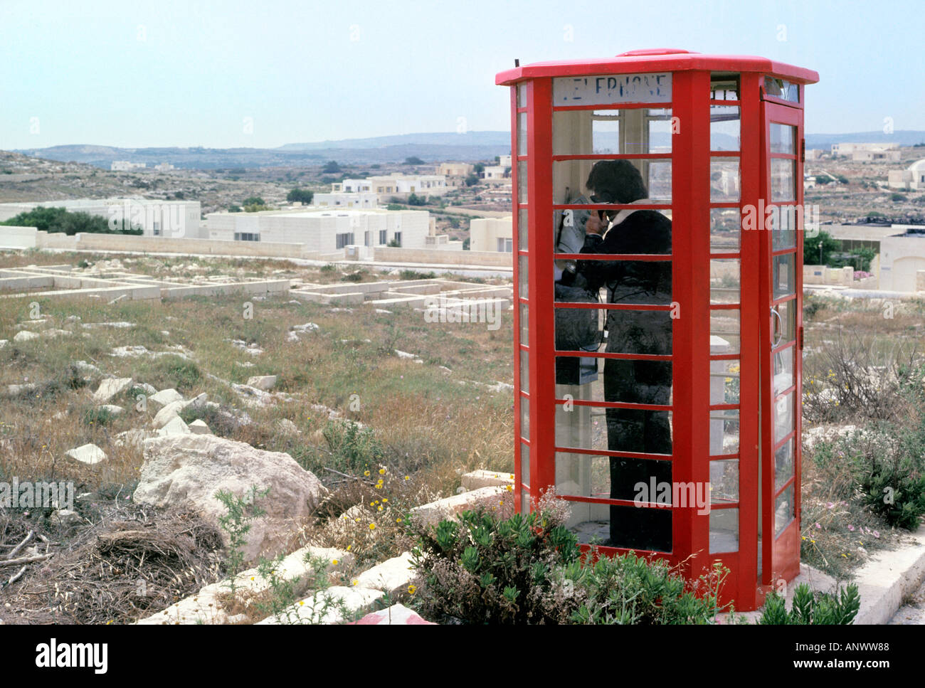 Man making a call from a public local red telephone box with holiday villas in background - Stock Image