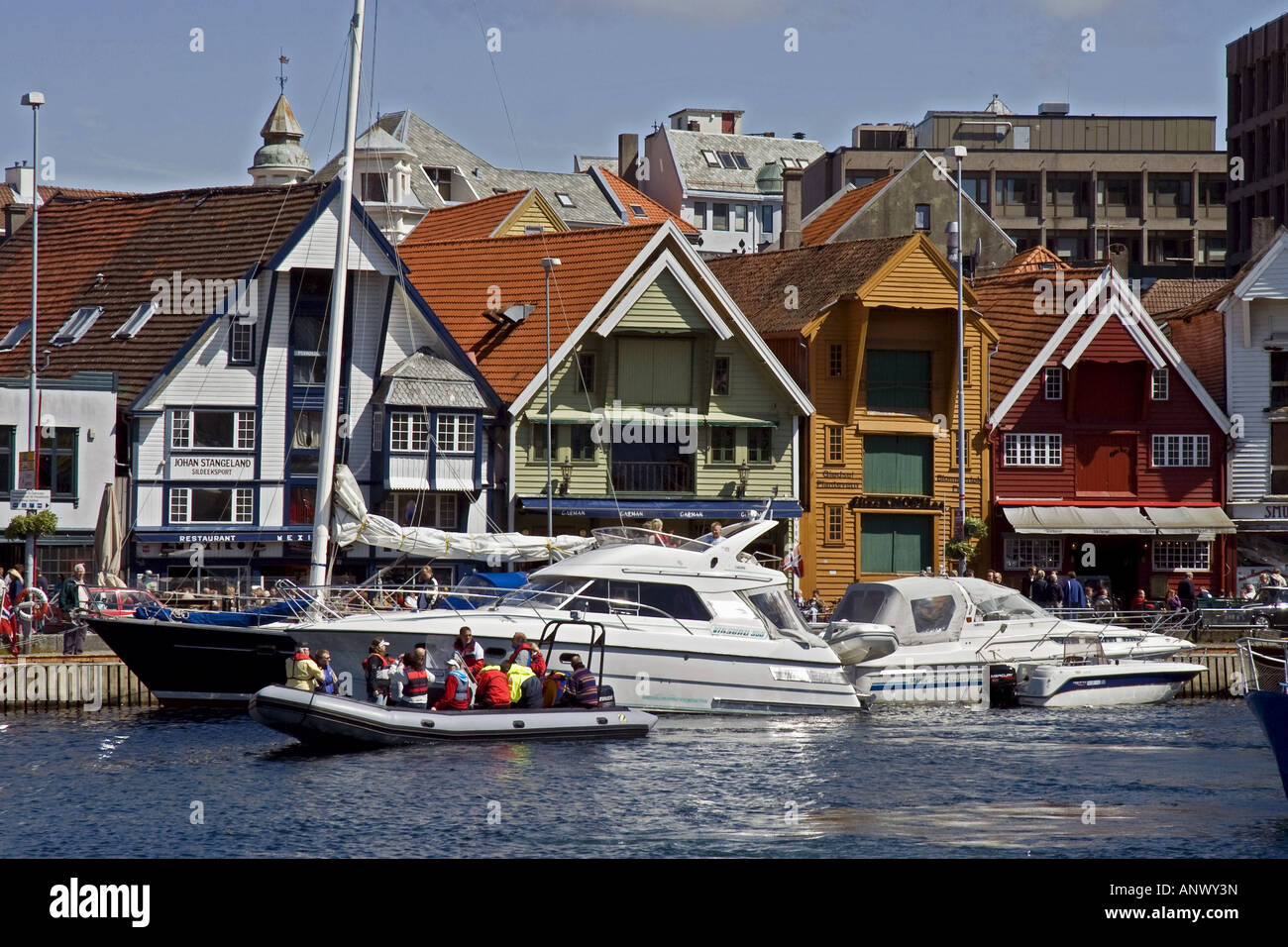 Boats, old buildings and people in the harbour of central Stavanger, Norway - Stock Image