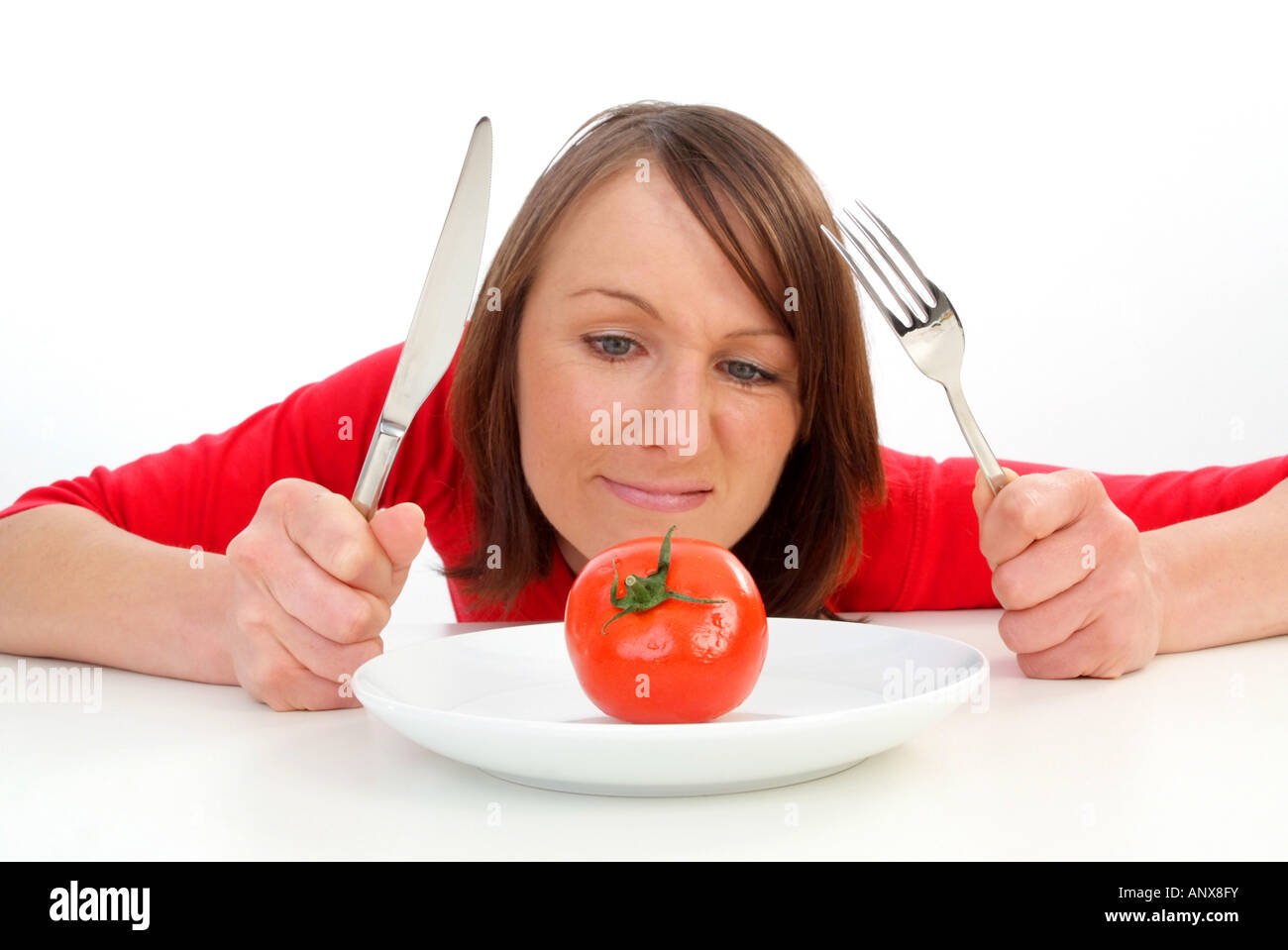 woman with tomato at plate Stock Photo