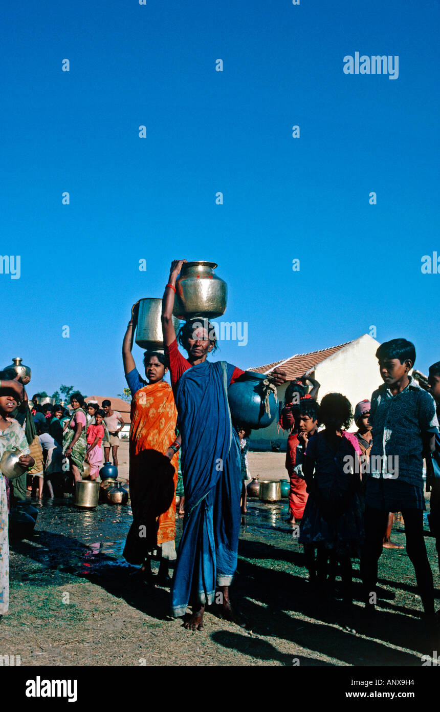woman carrying water mugs from water well village near town of mysore state of karnataka india - Stock Image