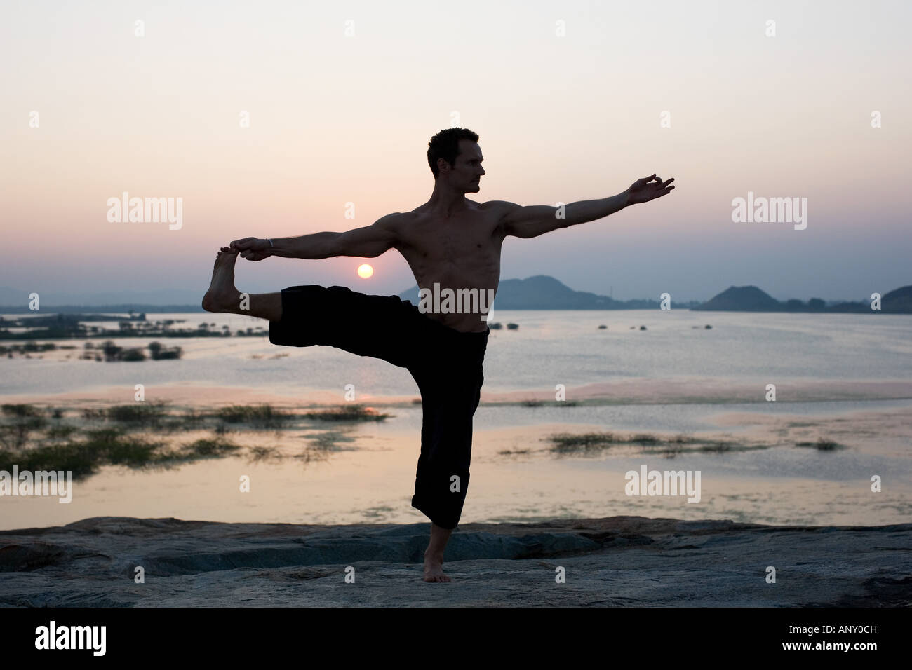 Silhouette of a man performing Hatha Yoga, utthita hasta padangusthasana, extended hand to big toe posture in India - Stock Image