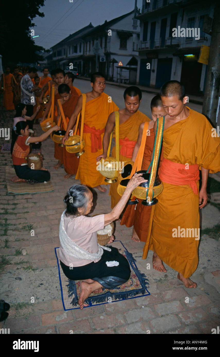 Laos, Luang Prabang Province, Luang Prabang. Monks collecting alms at dawn. Stock Photo