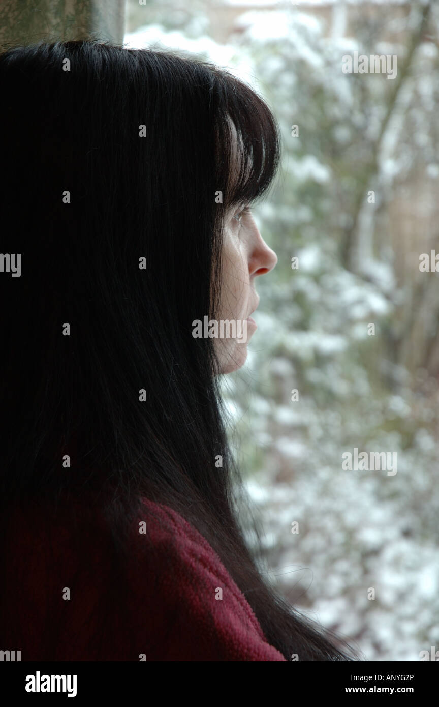 UK, England, woman gazing out of window in winter - Stock Image