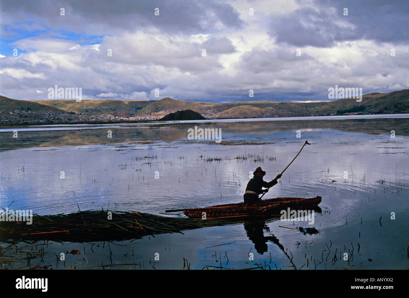 man of uros tribe riding totora reed boat at evening lake titicaca border area of peru and bolivia - Stock Image