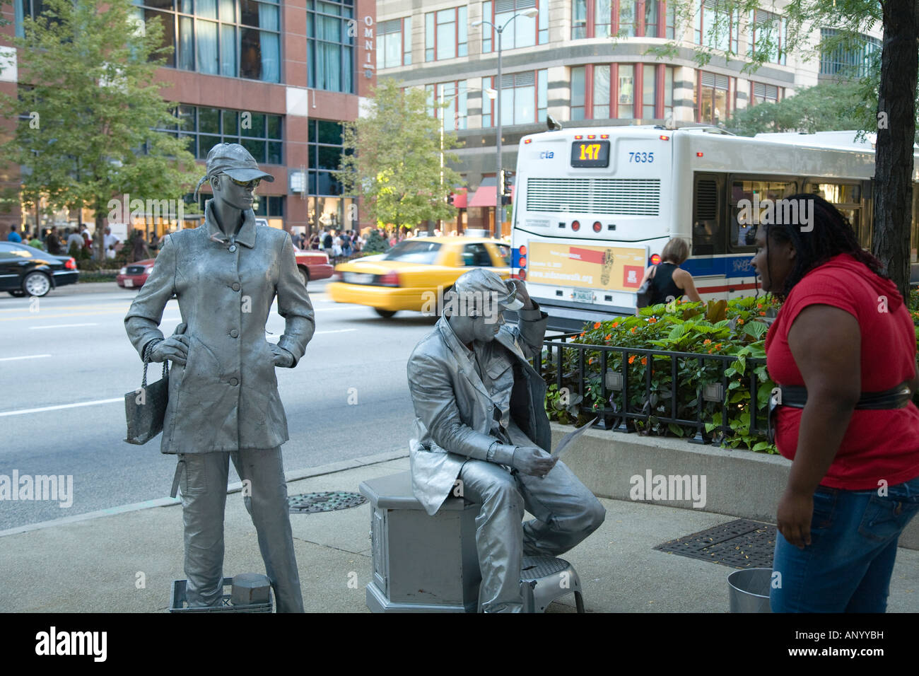 ILLINOIS Chicago Man and woman street performers in silver makeup sidewalk standing and sitting on sidewalk woman - Stock Image