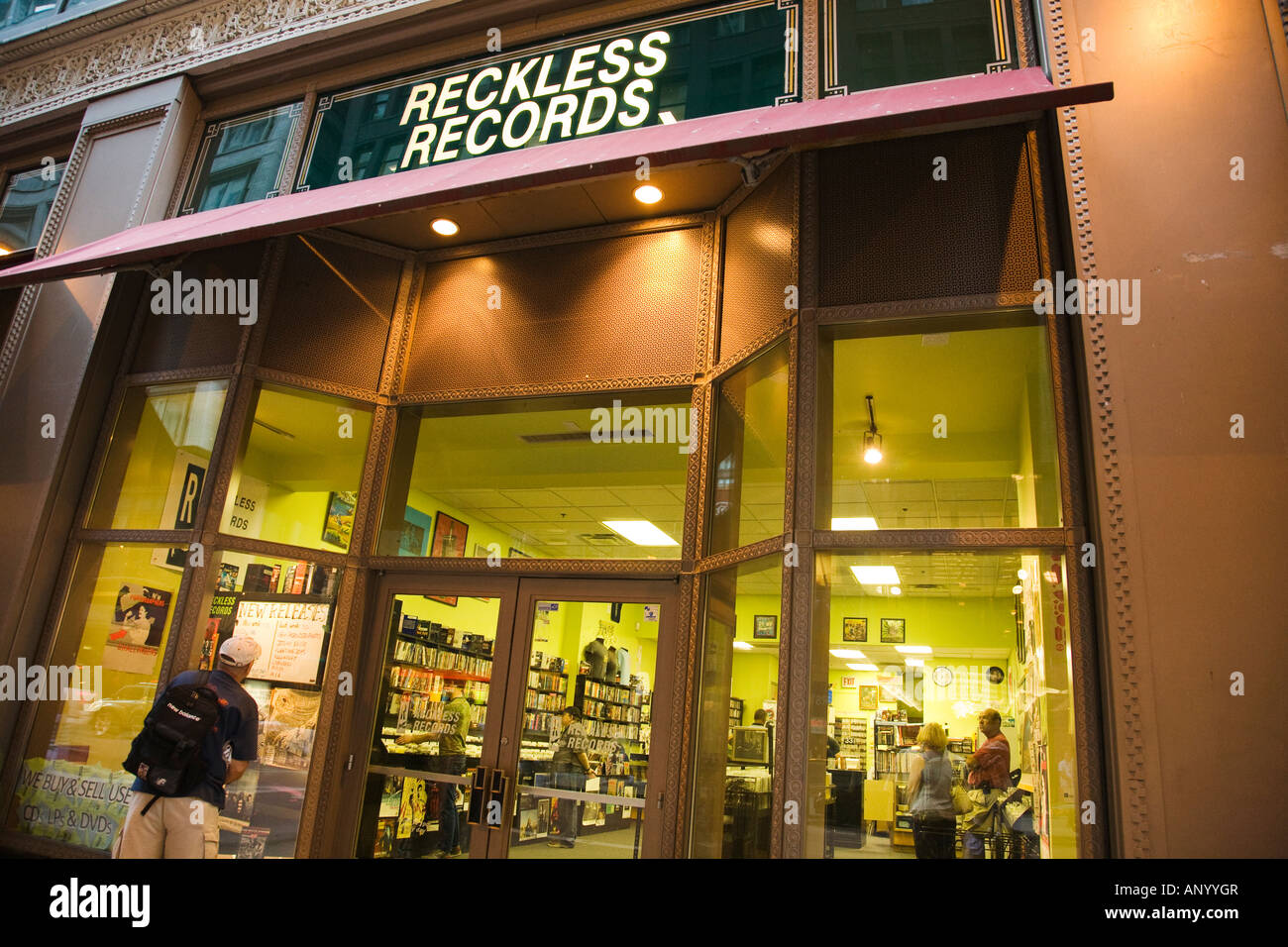 ILLINOIS Chicago Adult man look in store window of Reckless Records retail  store Madison Street downtown
