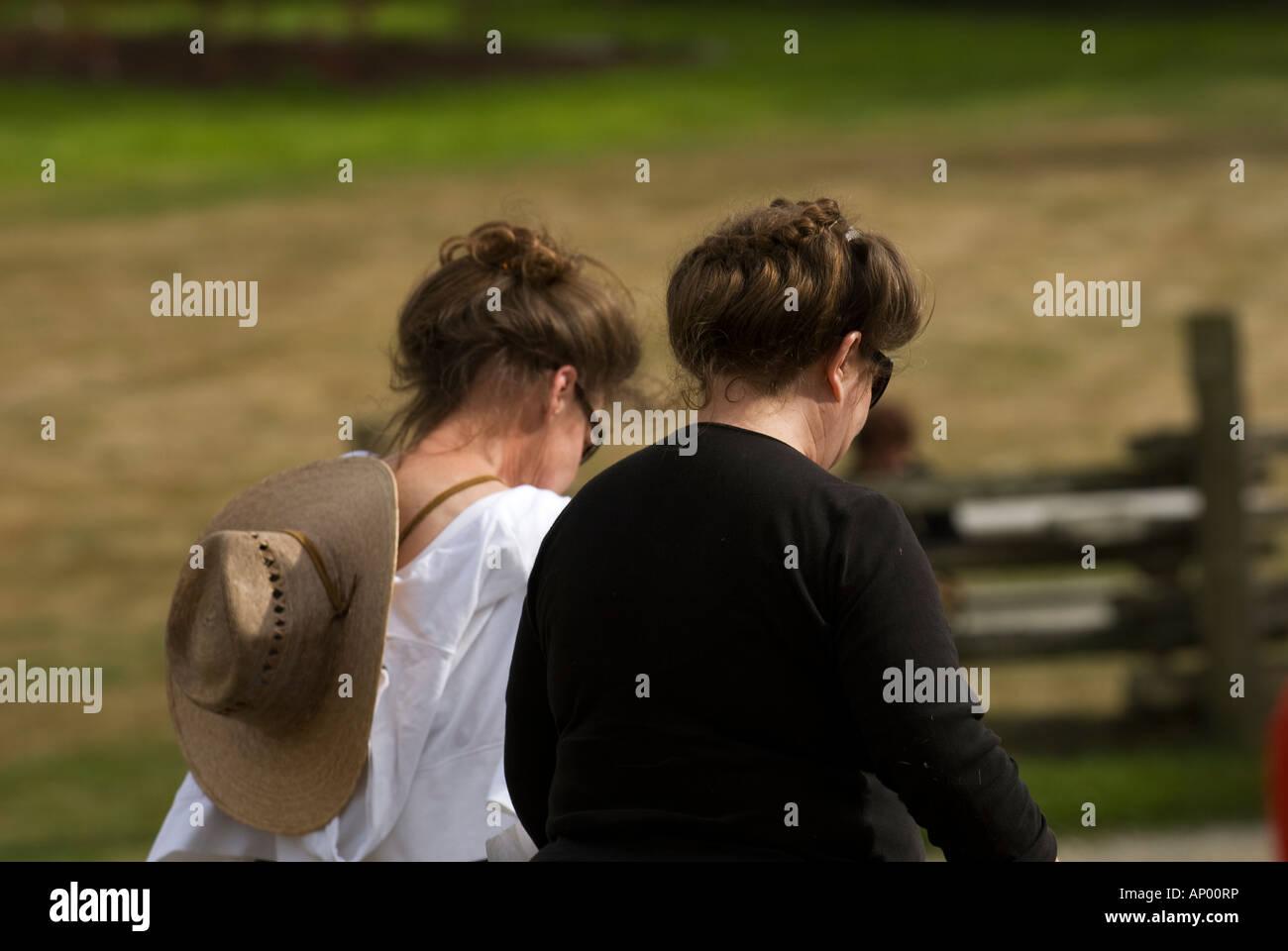 2 middle aged women look-alike walking towards fence - Stock Image