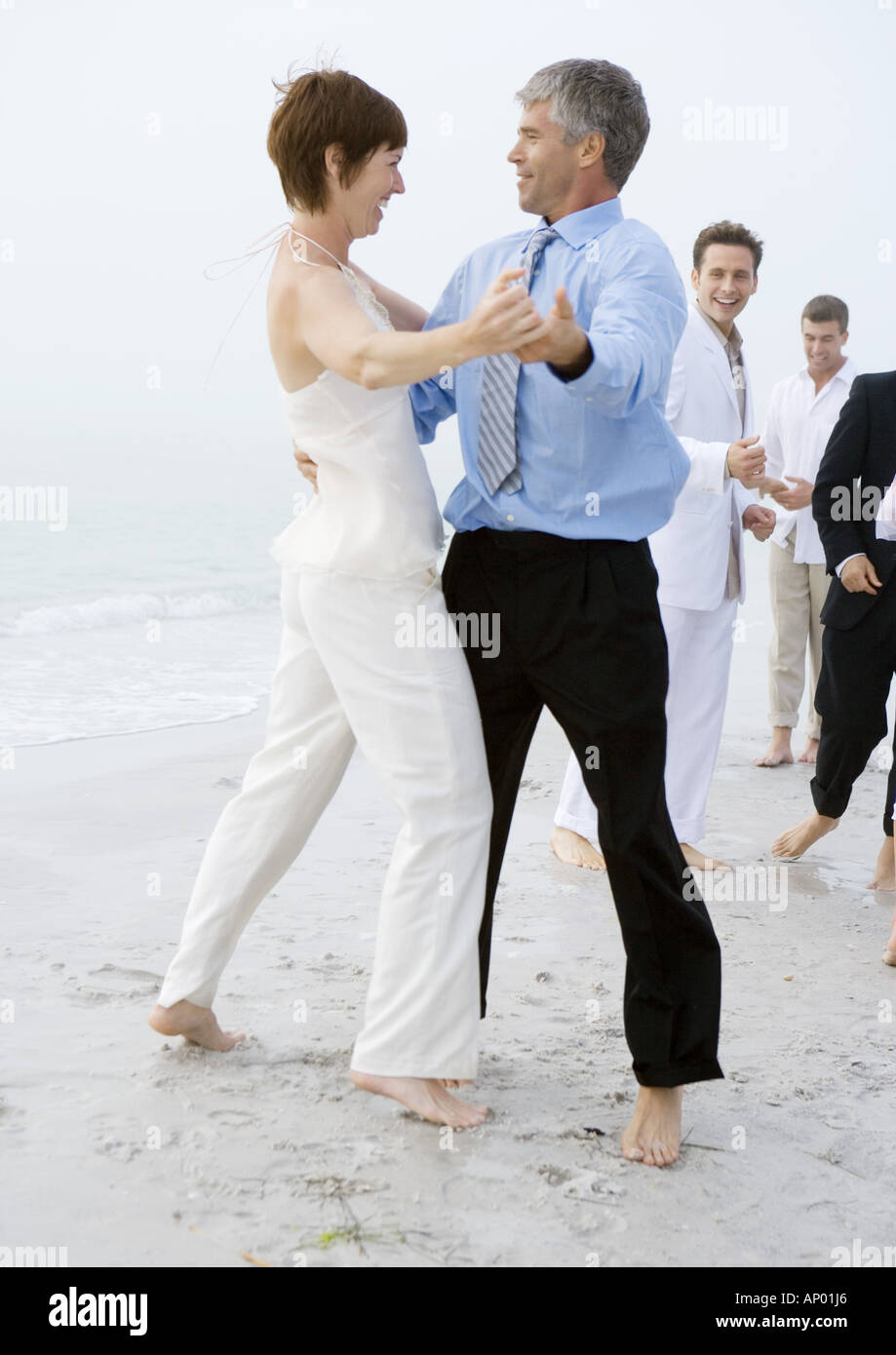 People in formalwear dancing on beach - Stock Image