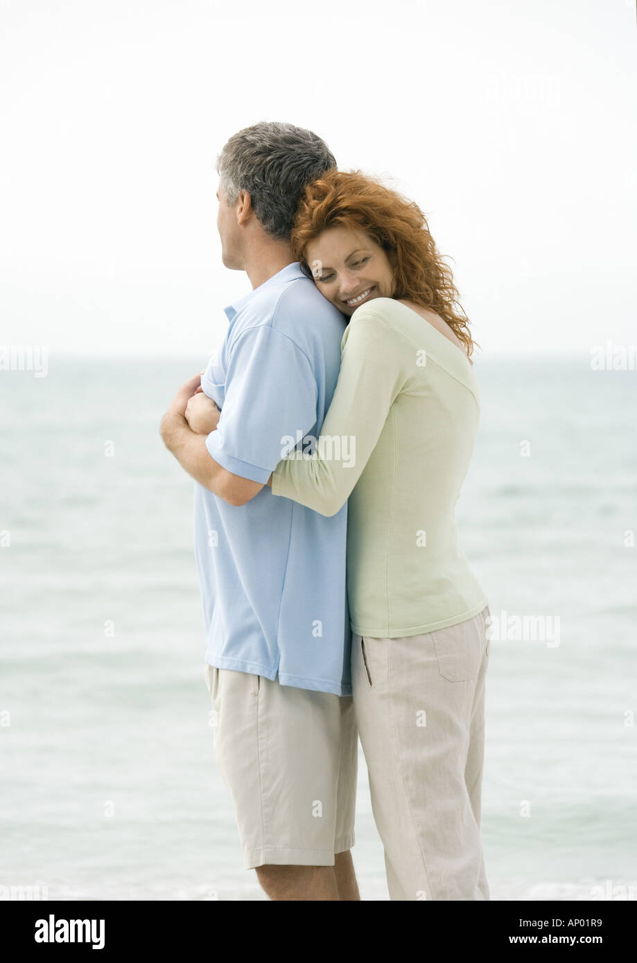 Mature couple, woman hugging man from behind - Stock Image