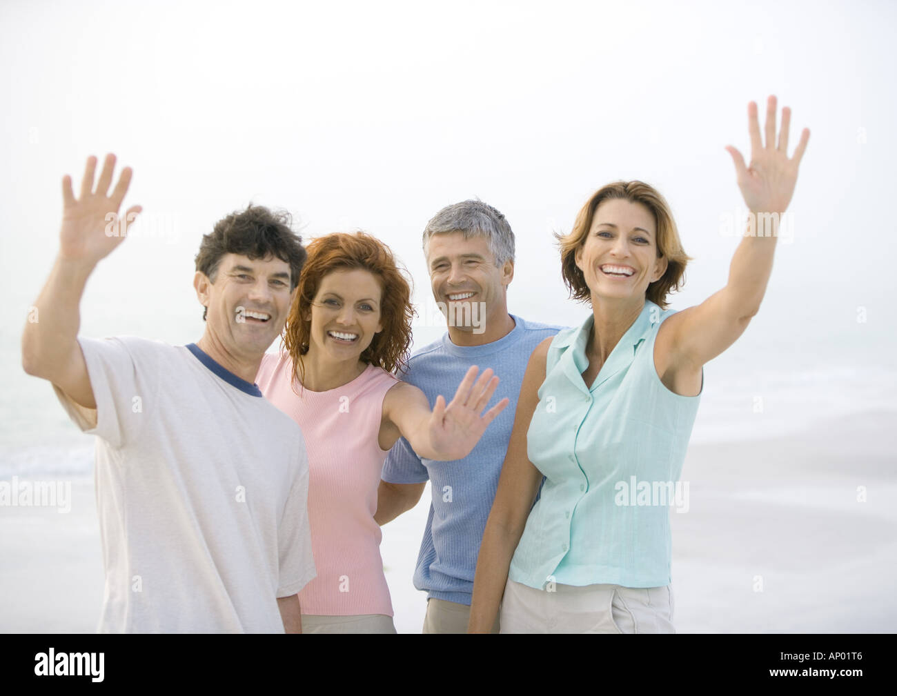 Two mature couples waving on beach - Stock Image