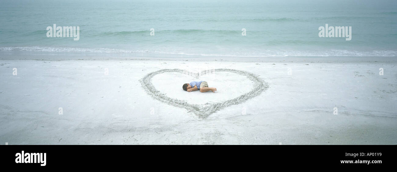 Child lying inside heart drawn on beach - Stock Image