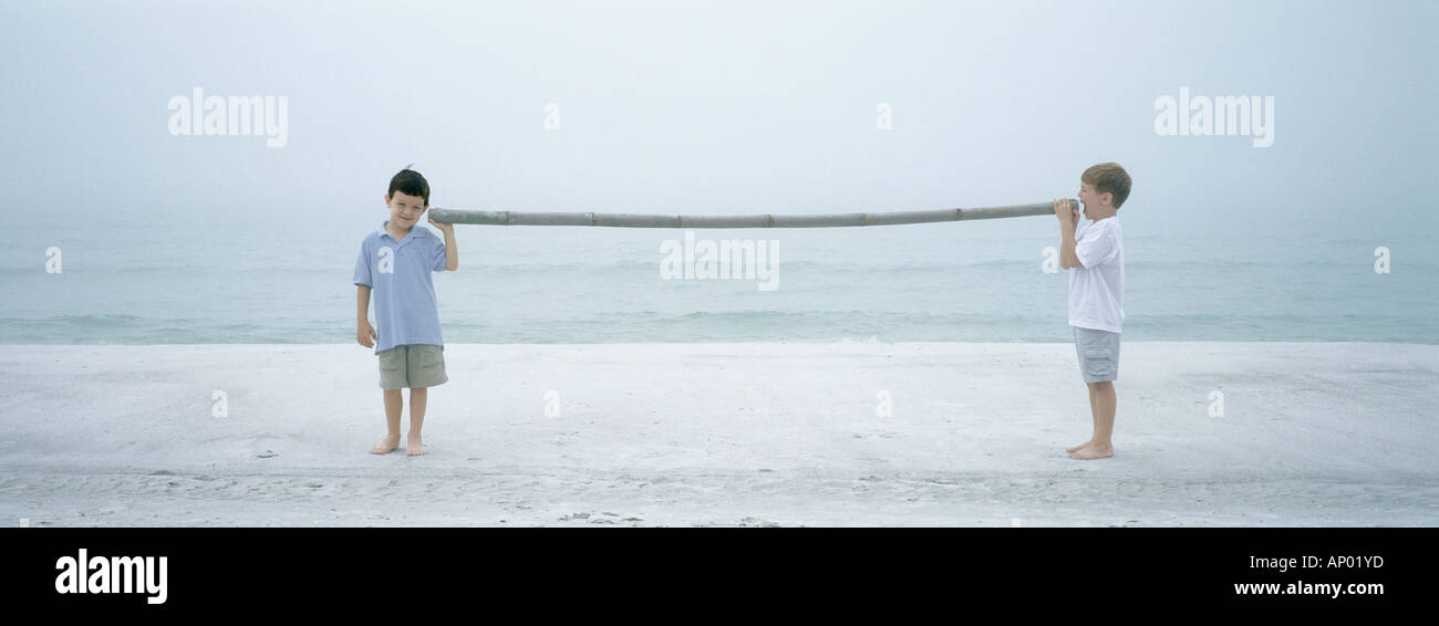 Boys speaking through stick on beach - Stock Image