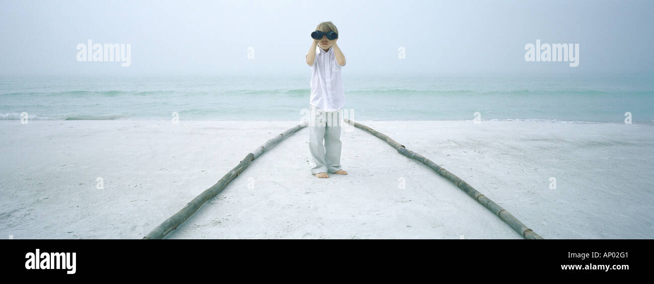 Boy looking through binoculars on beach - Stock Image