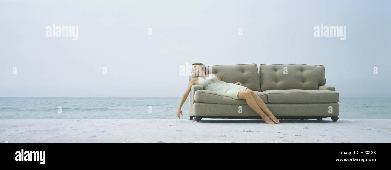 Woman reclining on sofa, on beach - Stock Image
