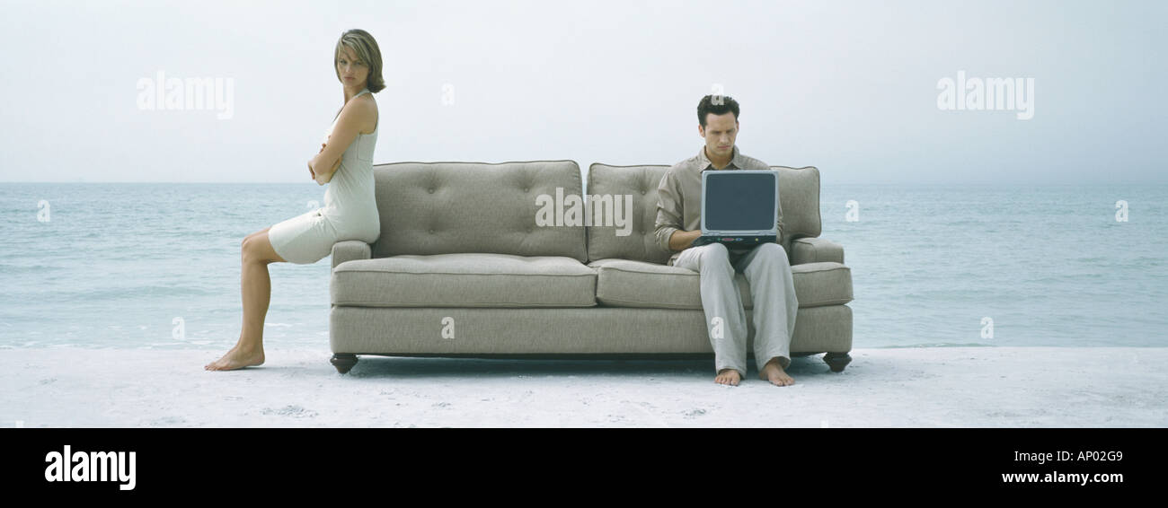 On beach, couple sitting apart on sofa - Stock Image