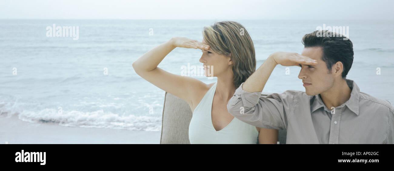 Couple looking toward distance on beach - Stock Image