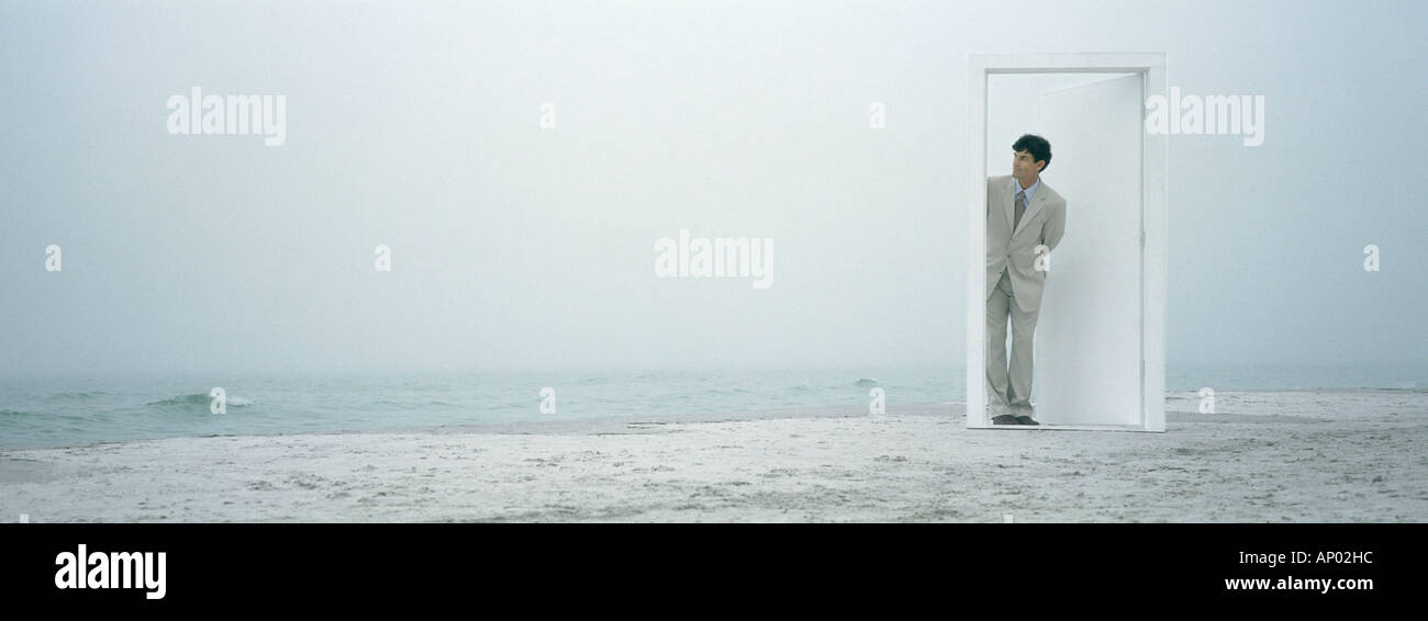 Man peeking through doorframe on beach - Stock Image