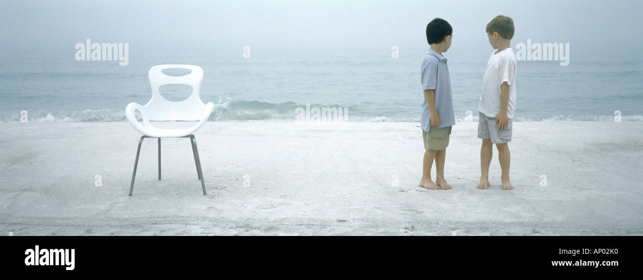 Two boys standing on beach, looking over shoulders at ocean - Stock Image
