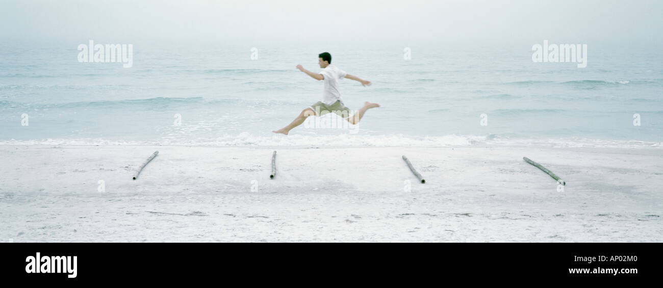 Man running and jumping over logs on beach - Stock Image