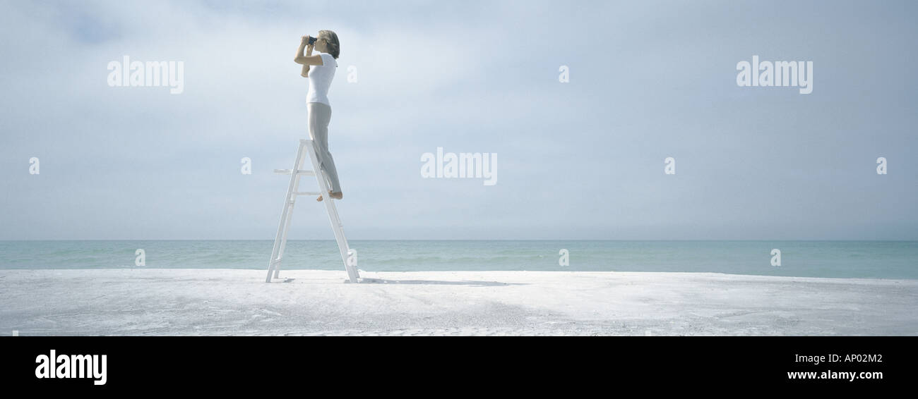 Woman standing on ladder, looking through binoculars, on beach - Stock Image